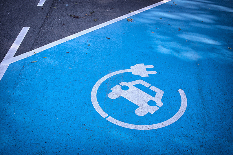 Logo 'charge your car here' on blue parking lot